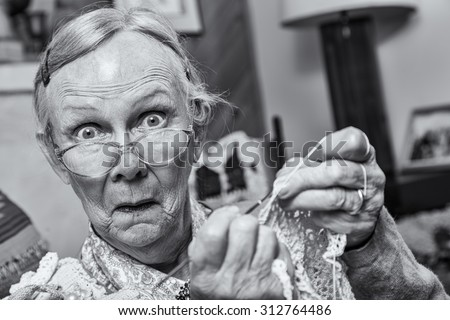 Surprised woman crocheting while looking at camera - stock photo