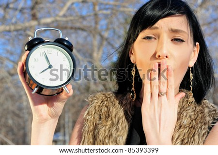Surprised woman holding alarm clock outdoors - stock photo