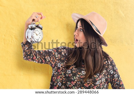 Surprised woman holding vintage clock over textured background  - stock photo