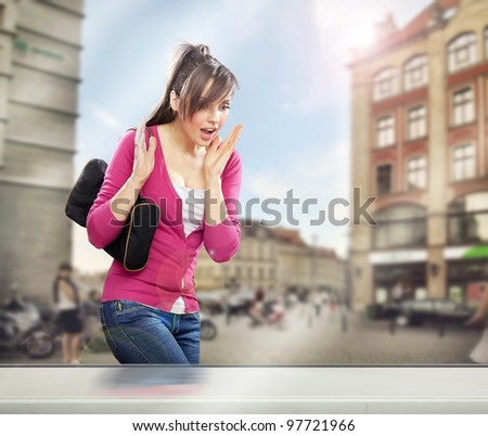 Surprised woman looking at a shop window - stock photo