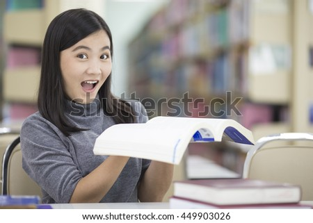 Surprised woman reading a book in the library - stock photo