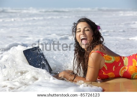 surprised woman using laptop in sea waves