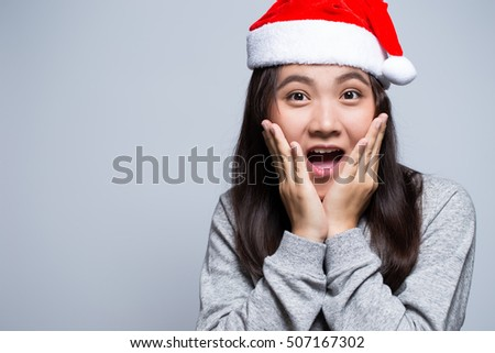 Surprised woman wearing a santa hat on isolated background
