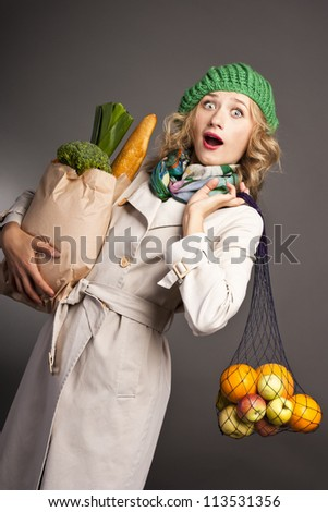 Surprised woman with a big bag of healthy food. against black background - stock photo