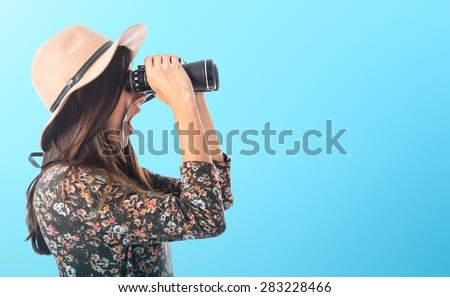 Surprised woman with binoculars over colorful background - stock photo