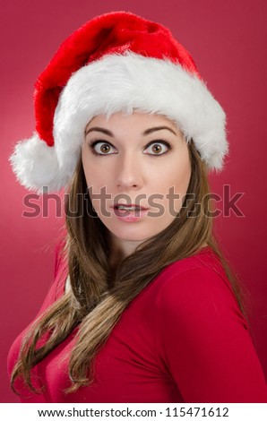 Surprised woman with santa hat on red background - stock photo