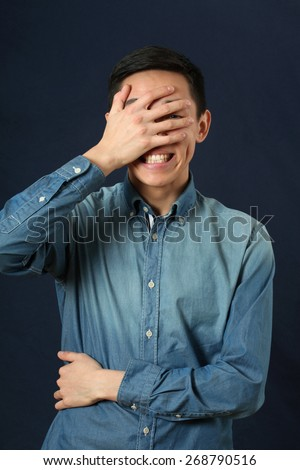 Surprised young Asian man covering his face by palm - stock photo