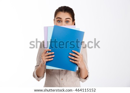 Surprised young beautiful brunette businesswoman holding colorful folders over white background