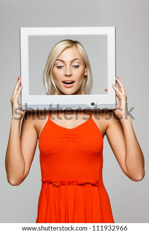 Surprised young blond female looking through the TV / computer screen frame, looking down, over gray background