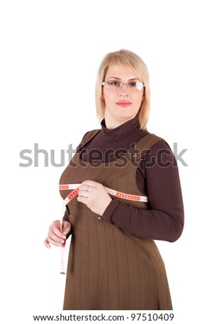 surprised young blond woman measuring her bosom - stock photo