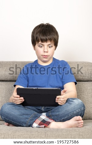 Surprised young boy and a tablet digital Surprised Young boy with eyes wide open using tablet digital on the sofa.  - stock photo