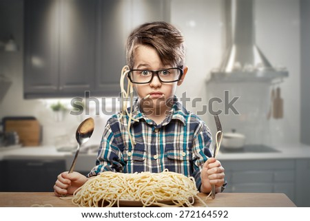 Surprised young boy in glasses with spaghetti - stock photo
