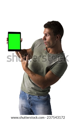 Surprised young man holding and showing ebook reader, standing isolated on white background - stock photo