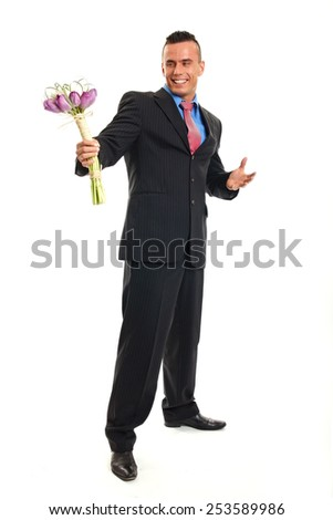 Surprised young man in suit poses with bouquet of tulips