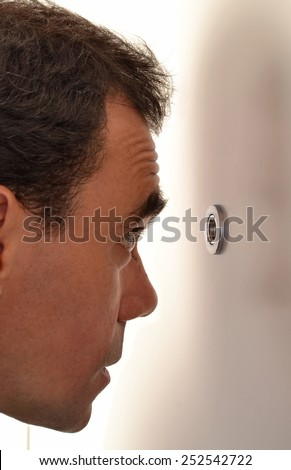 Surprised young man looking out through the peephole of his front door. - stock photo