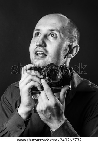 surprised young man photographed on antique film camera - stock photo