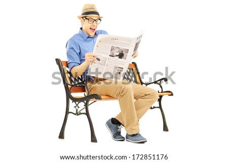 Surprised young man reading the news seated on a bench isolated on white background - stock photo