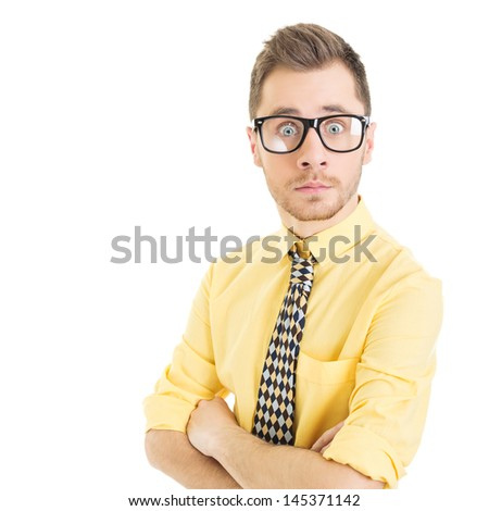 Surprised young man wearing yellow shirt and green bowtie
