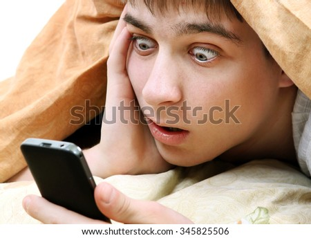 Surprised Young Man with Cellphone under Blanket on the Bed - stock photo
