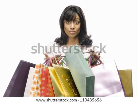 Surprised young woman carrying shopping bags - stock photo