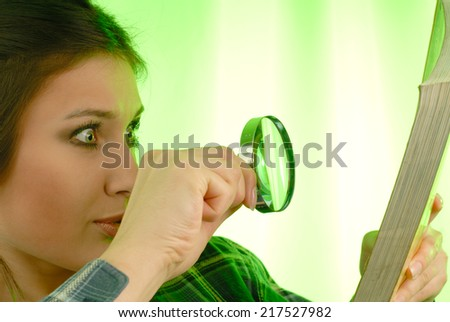 Surprised young woman considering a book with magnifying glass