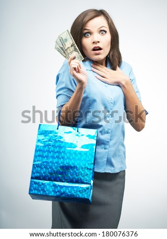 Surprised young woman in a blue blouse. Holds a gift bag and money. On a gray background