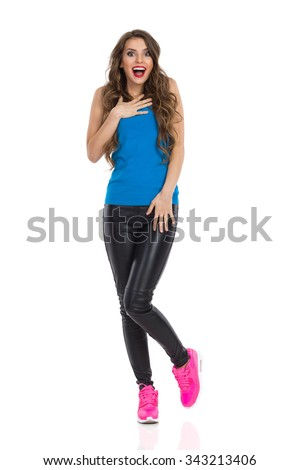 Surprised young woman in blue shirt, black leather trousers, and pink sneakers standing on one leg, holding hand on chest and looking at camera. Full length studio shot isolated on white. - stock photo