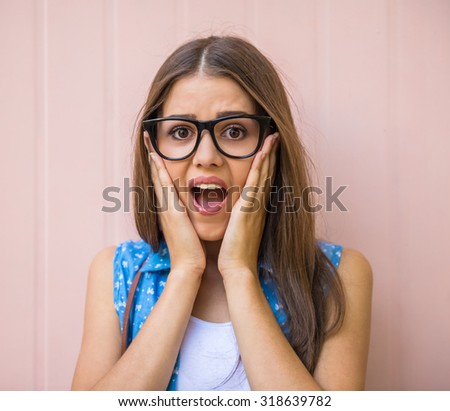 Surprised young woman in glasses is holding hands on face. - stock photo