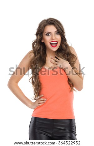 Surprised young woman in orange shirt shouting, holding hand on chest and looking at camera. Waist up studio shot isolated on white. - stock photo