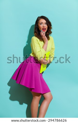 Surprised young woman in pink skirt and lime green blouse holding hand on chin and looking away. Three quarter length studio shot on teal background. - stock photo