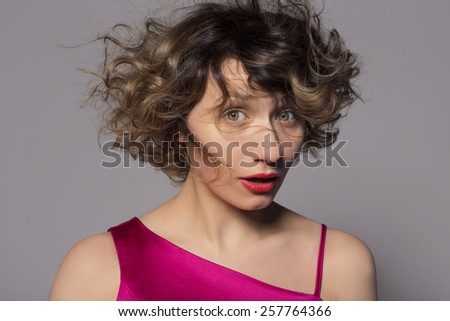 Surprised young woman looking at the camera - stock photo