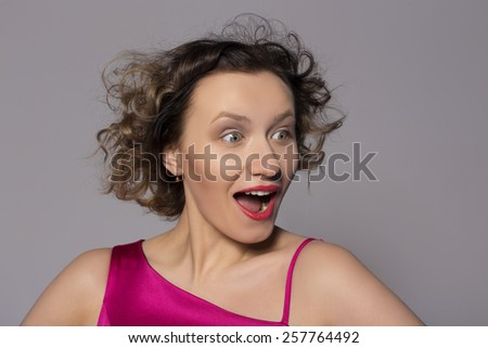 Surprised young woman. looking away - stock photo