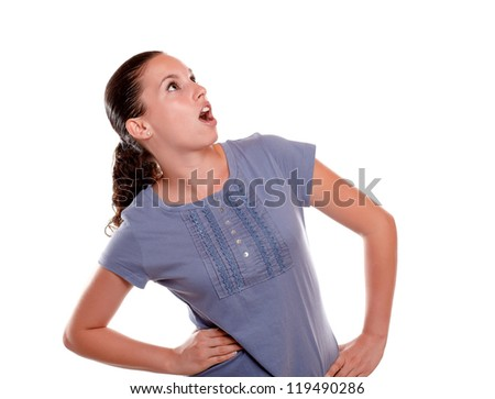 Surprised young woman looking to her left up on blue blouse against white background - copyspace - stock photo