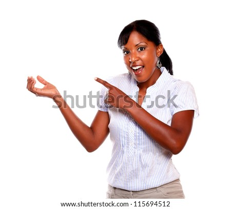 Surprised young woman pointing to her right hand against white background - stock photo