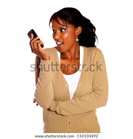 Surprised young woman reading a message on cellphone against white background