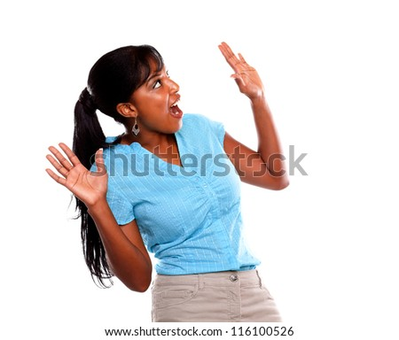 Surprised young woman screaming and looking up on blue shirt on isolated background - copyspace - stock photo