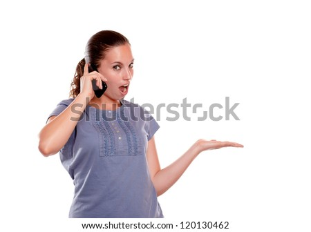 Surprised young woman speaking on mobile phone on blue shirt standing over white background - stock photo