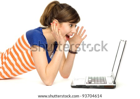 Surprised young woman using laptop - stock photo