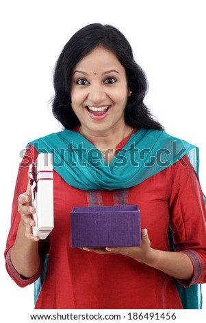 Surprised young woman with gift box against white background