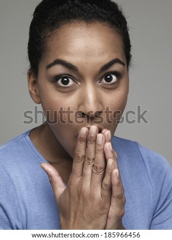 Surprised young woman with hands on mouth