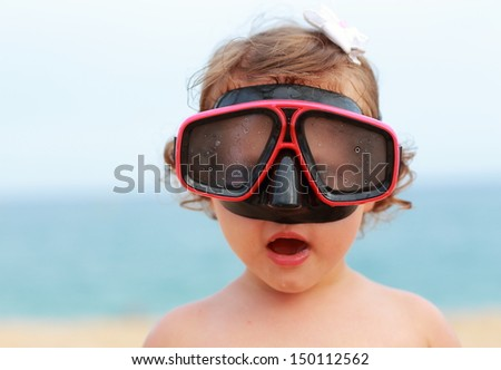 Surprising baby girl in diving mask looking fun on blue sea background - stock photo