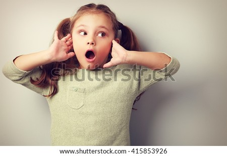 Surprising kid girl with long hair with opened mouth and hand near face looking. Toned portrait - stock photo