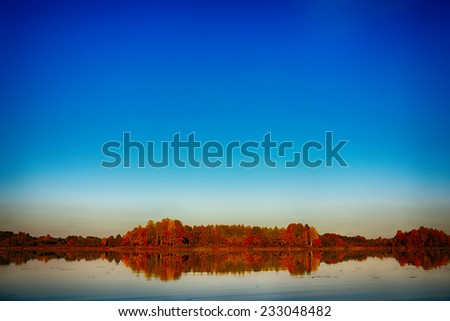 Surreal autumn of yellow trees with reflection on lake - stock photo