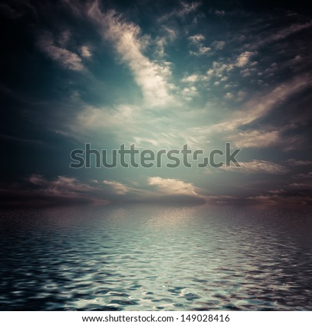 Surreal, dark clouds reflected in water surface.  Color toned image. - stock photo