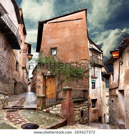Surreal house and cobblestone village street at evening - stock photo