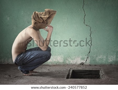 Surreal image with bag over his head shirtless and blue jeans - stock photo