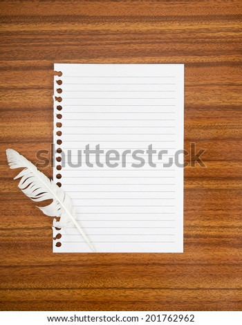Surrender note with white feather. Lined torn sheet of paper, blank for your message. On desk. - stock photo