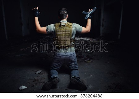 Surrendering man in military uniform holding a gun - stock photo