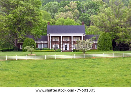 Surrounded by Spring green, this brick two story home and grounds are neat as a pin.  Home is surrounded by the Appalachian mountains and a pasture of green grass. - stock photo