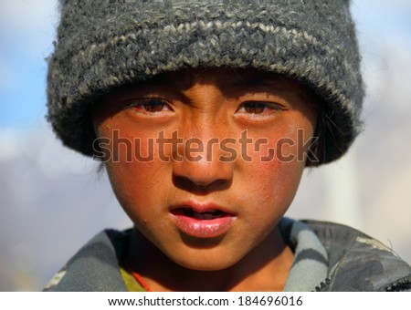 SURU, INDIA - JUNE 23: Young Tibetan boy Sonam, 9, poses for a photo on June 23, 2013 in Suru valley, Jammu & Kashmir, Northern India. There are many Tibetan refugees living in Ladakh. - stock photo